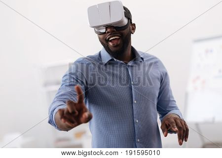 3d reality. Nice positive pleasant man wearing 3d glasses and looking at the virtual screen while being in 3d reality