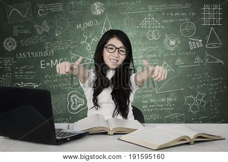 Image of Asian female student showing thumbs up while studying in the class with doodles on the chalkboard