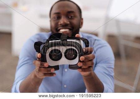 Progressive innovations. Selective focus of modern 3d glasses being shown to you by a nice delighted handsome man