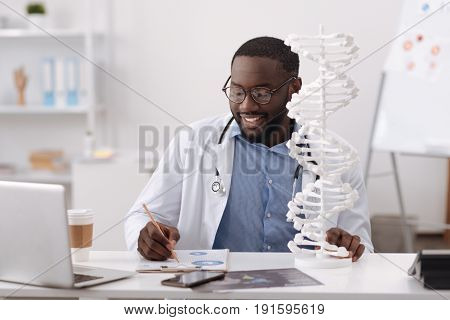 Genetic studies. Intelligent smart handsome scientist sitting at the table and taking notes while studying genetics