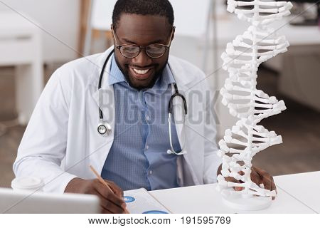 Modern genetics. Smart nice male scientist taking notes and smiling while studying genetics
