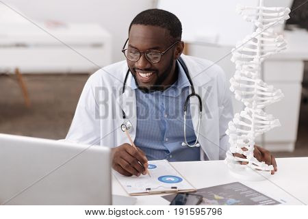 DNA studies. Cheerful professional handsome scientist sitting at the table and looking at the laptop screen while doing a genetic research