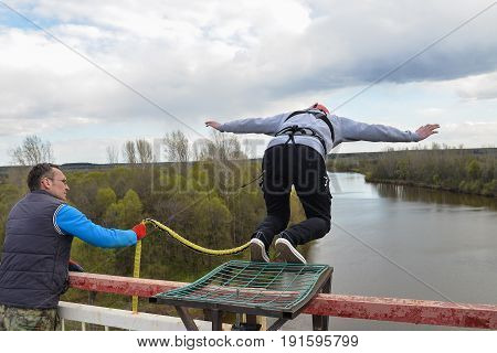 Russia, Izhevsk, May 14 2017.Jumping with a rope from high altitude of bridge on Izh river