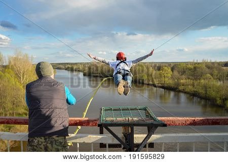 Rope jumping from high altitude of bridge. Brave woman flying in air like a bird