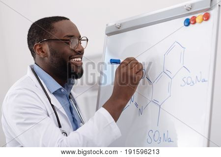 Time for chemistry. Handsome positive male chemist smiling and looking at the whiteboard while writing a formula