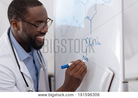 Chemistry studies. Handsome positive nice scientist holding a highlighter and writing a formula on the whiteboard while doing chemical research