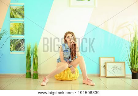 Beautiful young woman sitting on pouf at home