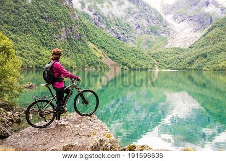 Biking woman in Norway against picturesque landscape
