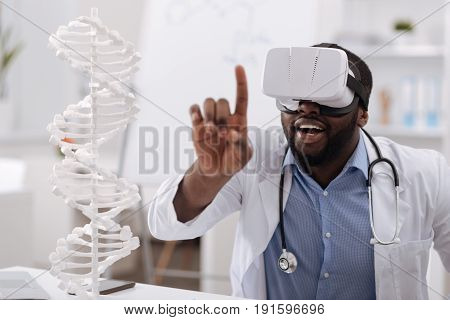 Innovation in genetics. Professional intelligent afro american scientist sitting at the table and studying genome while being in virtual reality