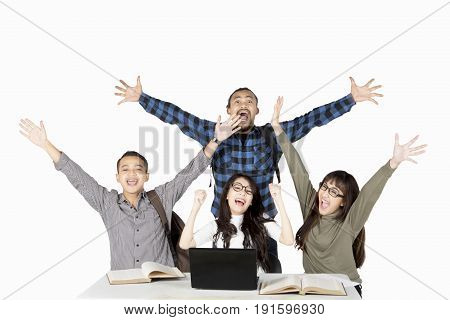 Image of diversity students lifting hands as their success expression with a laptop and book on the desk