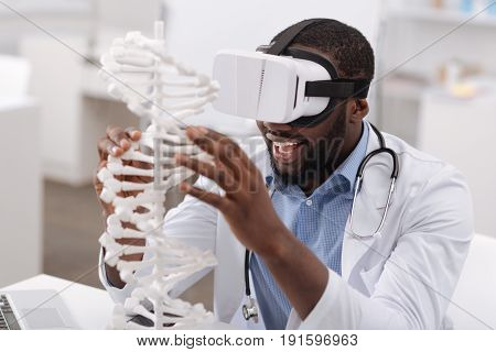Chromosome studies. Joyful happy enthusiastic man sitting at the table and touching the gene model while being in the virtual reality