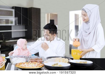 Happy family eating together in dining room while sitting in front of dining table