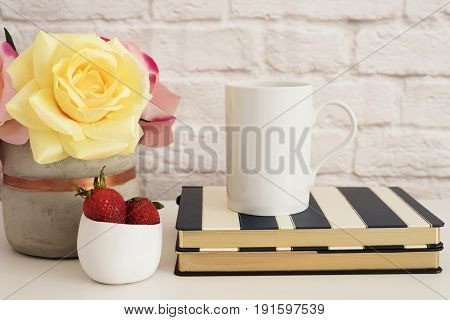 Coffee Cup Product Display. Coffee Mug On Striped Design Notebooks. Strawberries In Gold Bowl, Vase