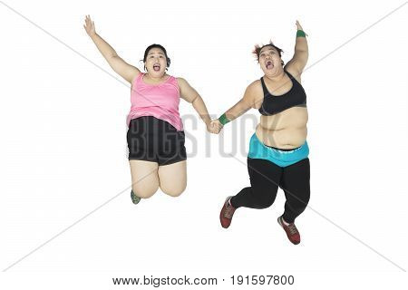 Two fat women leaping together while lifting their hands isolated on white background