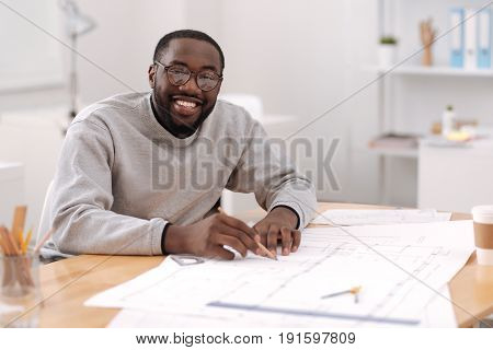 Modern engineering. Happy professional good looking engineer holding a pencil and doing a drawing while being involved in his project