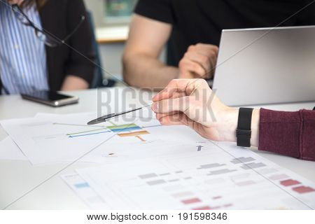 Cropped image of businessman's hand pointing on chart on desk in office