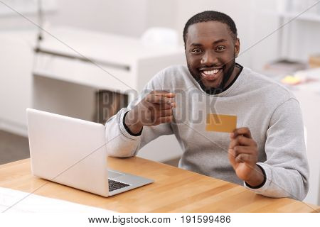 Electronic banking. Handsome delighted nice man pointing at the credit card and smiling while using electronic banking