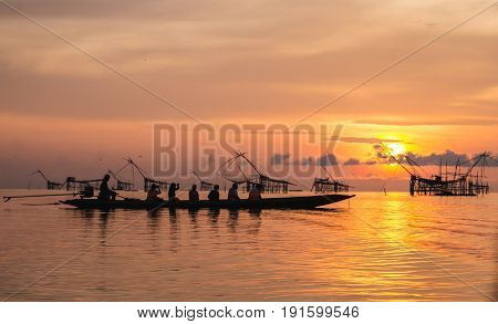 Sunrise at Pak Pra lakePattalungThailand. Silhouette of traditional fishing method using a bamboo square dip nettraveler on the boat.