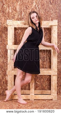 Full length woman fashion style posing on wooden wall in studio photo. Style and vogue