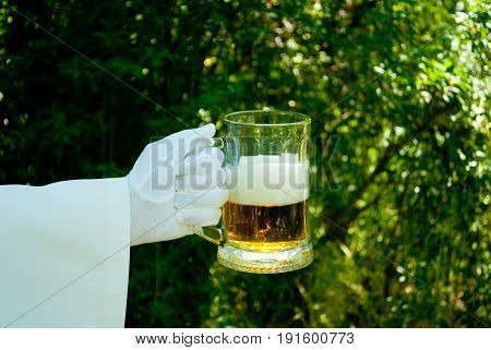 The waiter's hand in a white glove and with a white napkin holds a half-filled beer and a foam beer glass in the blurred background of the nature of the trees and bushes