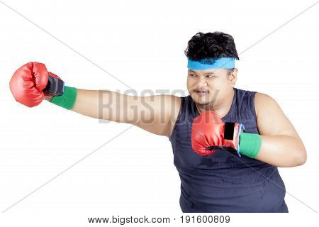 Portrait of a young overweight man doing boxing exercise while wearing boxing gloves and sportswear isolated on white background