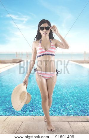 Summer Concept. Full length of a pretty woman walking near a swimming pool while wearing a striped swimwear and sun glasses shot with beach view