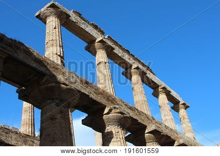 columns of an ancient amphitheatre on the background of blue sky
