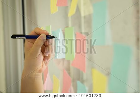Sticky note paper reminder schedule on window. Use post it notes to share idea on sticky note. Discussing - business teamwork brainstorming concept with film vintage tone.