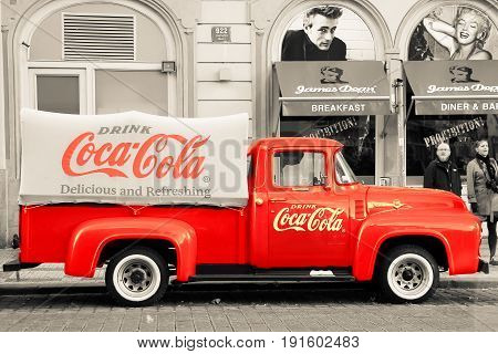 PRAGUE, CZECH REPUBLIC - Oct 23 2015: An old renovated red Ford vintage Coca cola truck (pickup) in a parking lot., black and white, sepia, colorization