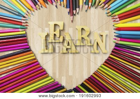 Education concept. Top view of sharp color pencils shaped heart symbol with Learn text