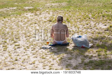 Summer sunny day. A lonely girl is sitting on the grass at a forest lake