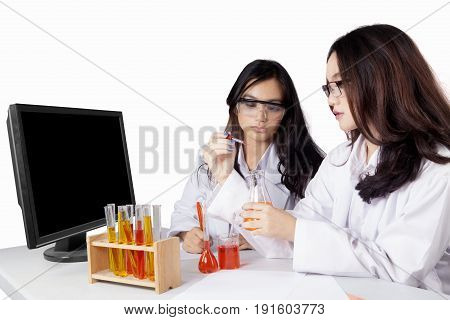 Two pretty female high school students doing chemical experiment with test tube and chemical liquid