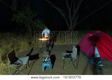 Woman Cooking With Fire Wood And Braai Equipment By Night. Tent And Chairs In The Foreground. Advent