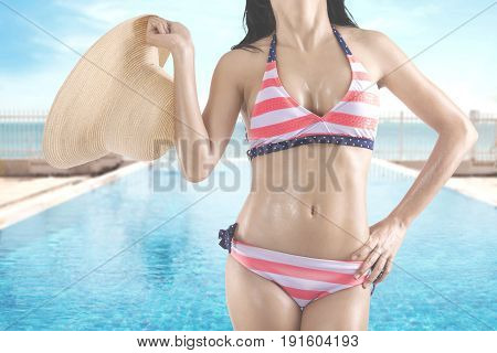 Summer Concept. Closeup of a young woman with beautiful body holding a straw hat while wearing a striped swimsuit and posing near a swimming pool with beach view