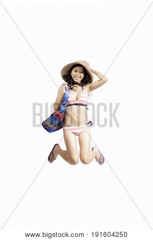 Young woman leaping while wearing bikini and beach items isolated on white background