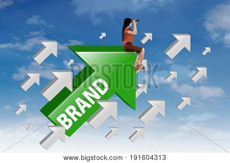 Businesswoman sitting on the upward arrow with brand word and looking at the sky through binocular