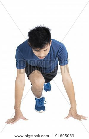 Young runner in starting position while wearing sportswear isolated on white background