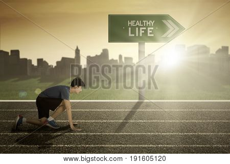 Young runner in ready position to run in the track with healthy life word on signpost