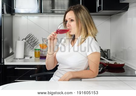 successful beautiful girl drinking red wine in the kitchen