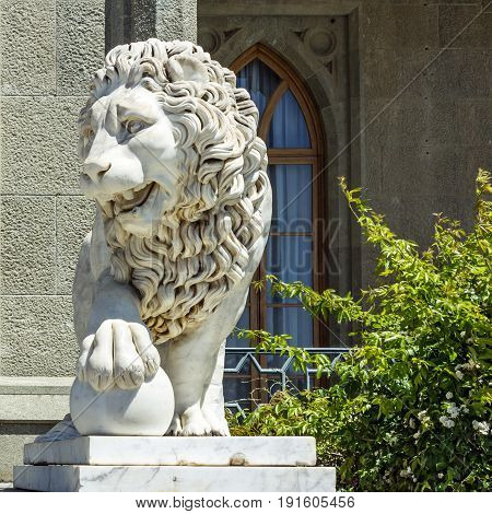 Marble sculpture of lion with ball in Vorontsov Palace in Alupka, Crimea, Russia.