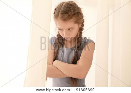 Displeased little girl near window at home