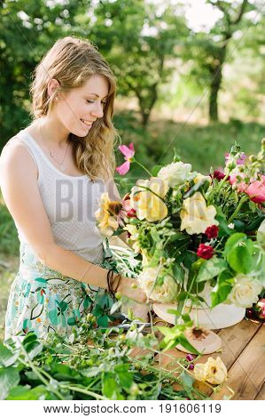 summer, beauty, lifestyle, arts and crafts, wedding concept - charming young woman with flowing fair hair standing nearby wooden garden table and making gorgeous bouquet composed of roses and peonies