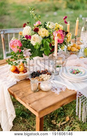 romance, love, wedding, holidays, decoration, rest concept - romantic table setting with bright multicolored bouquet in centre, white feast serveware, slender candles and fruits and nuts
