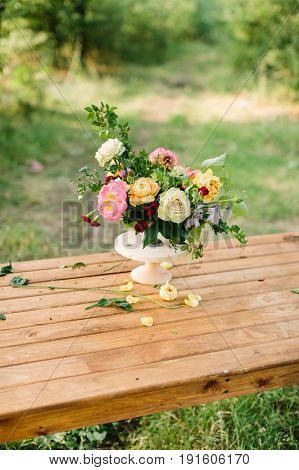 floral design, wedding, romance concept - gorgeous bouquet made of tender avalanches, roses, peonies and dianthuses, decorated with leaves of oak and raspberry-bush, standing in vase on wooden table
