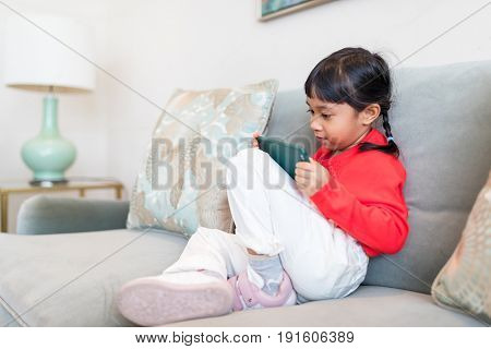 Little girl looking at cellphone at home