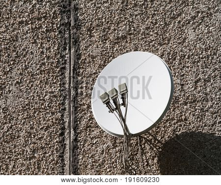 Sunny day. One white satellite dish on the background of the wall of the house