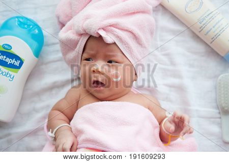 After baby cute girl is taking a bath. Baby portrait smiling and crying when get dress. Mother getting her baby girl dressed on May 28, 2017 in Bangkok, Thailand.