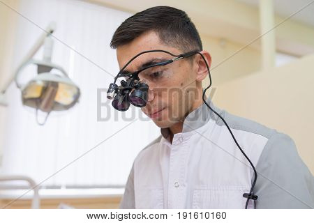 Young Caucasian Dentist wearing dental binocular loupes.