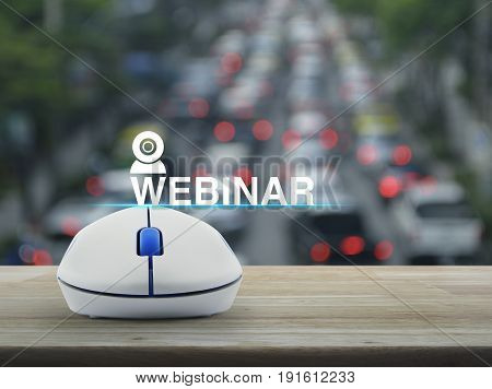 Webinar icon with wireless computer mouse on wooden table over blur of rush hour with cars and road Seminar online concept