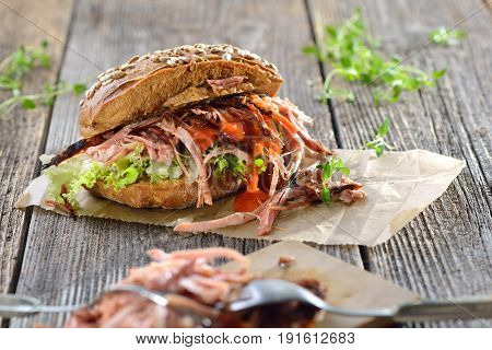 Street food: Barbecue pulled pork wholemeal sandwich with coleslaw, hot BBQ sauce served on brown wrapping paper on a wooden background